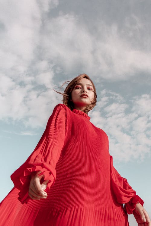Low Angle Photo of Woman in Red Long-sleeved Dress Posing