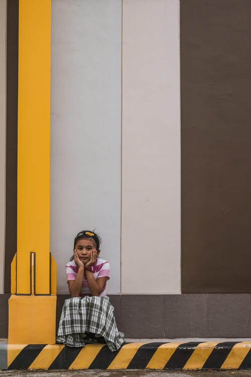 Photo of Sad Young Girl Sitting Alone by Curb