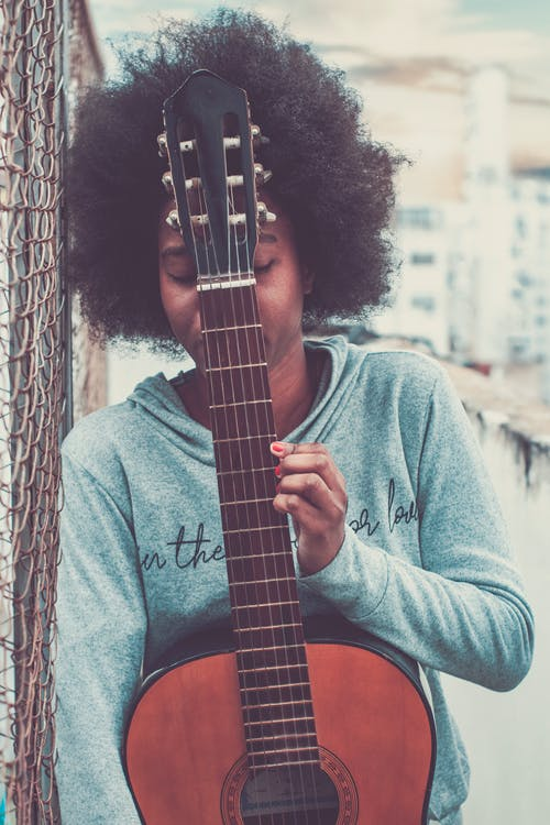 Unrecognizable African American female musician with closed eyes standing on street with acoustic guitar