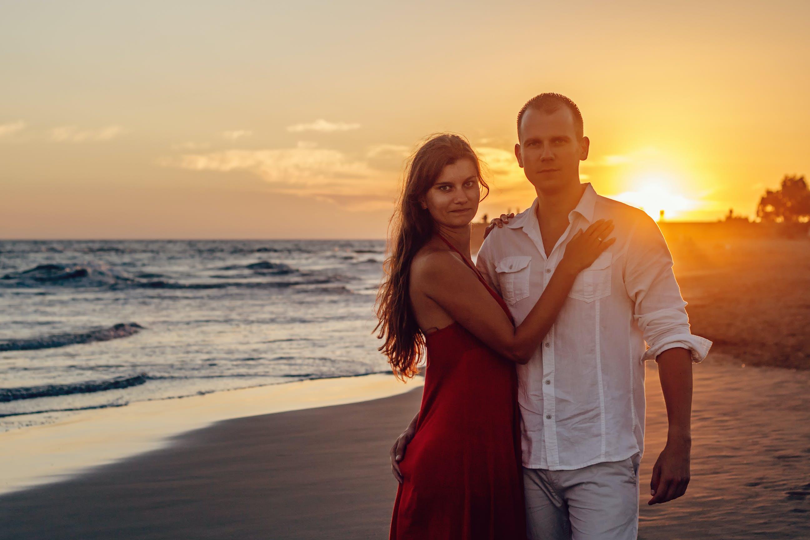 Woman Standing Beside Man Near Shoreline