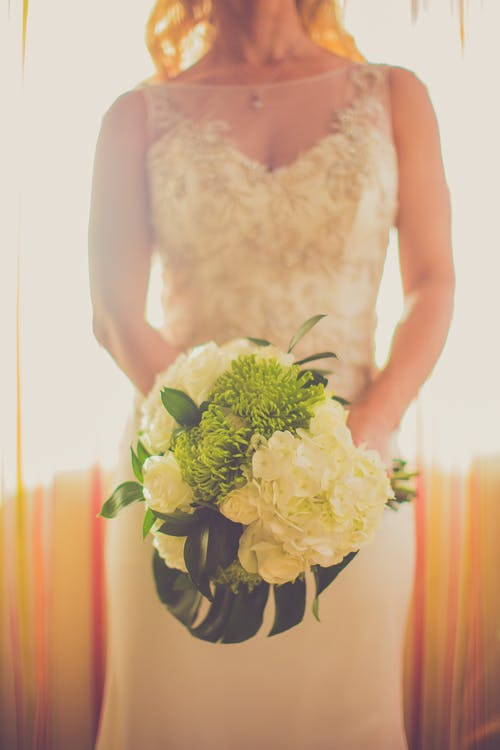 Close-up Photo Bride Holding Bouquet of Flowers