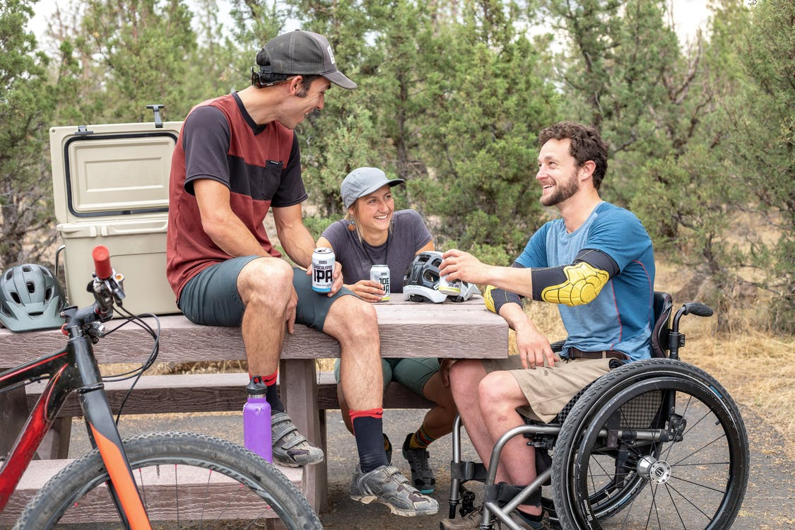 Group Of People picnic atable, one with a bike, one with a wheelchair