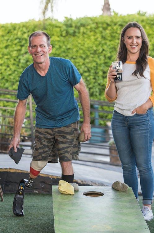 Man Playing Cornhole Beside a Woman Holding a Drink