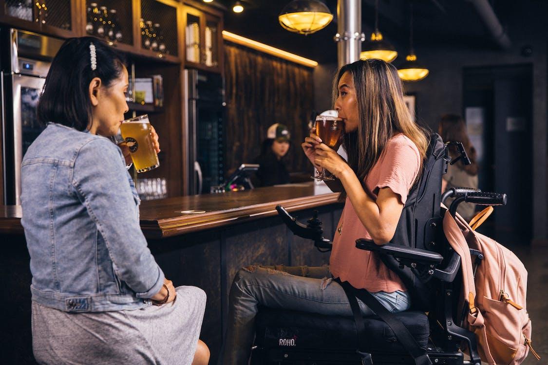 Two Sitting Women Drinking Beside Bar Counter