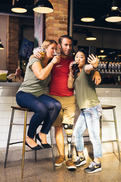 People Taking a Selfie While Drinking Beer