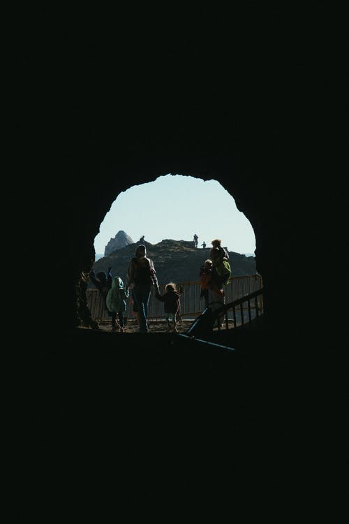 Woman Walking With Children Outside A Cave