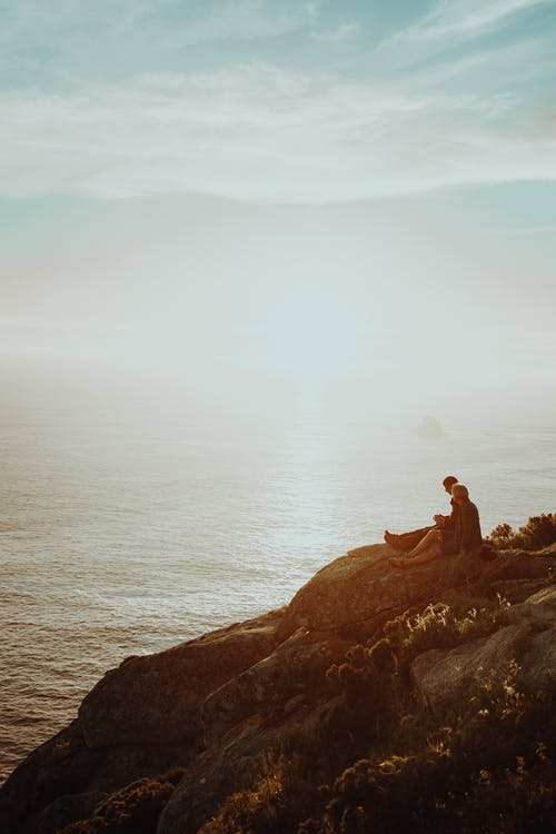 Two Persons Sitting on A  Cliff