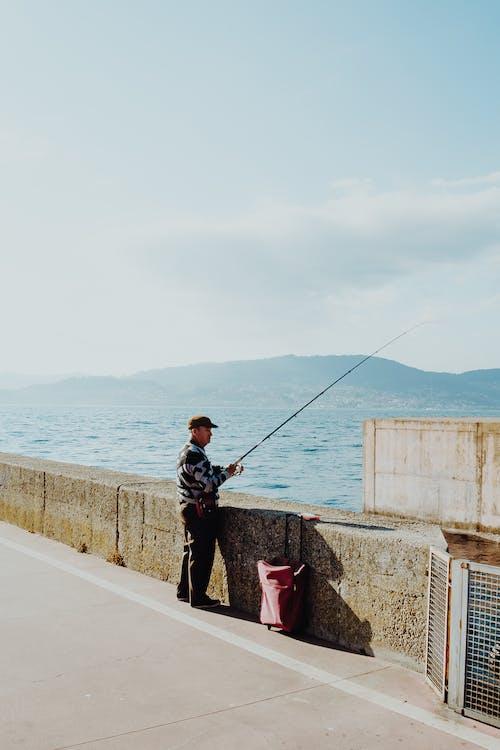 Man Standing Near Concrete Wall Holding Fishing Rod