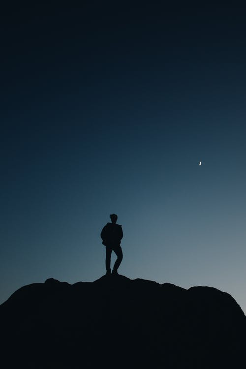 Silhouette of Man Standing on A Rock