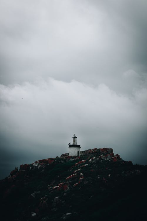 Lighthouse on  a Mountain Under Gray Sky