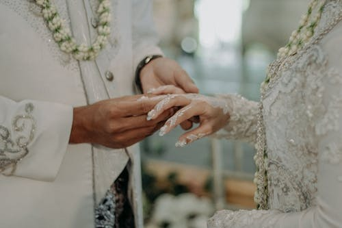 Groom Putting The Wedding Ring On The Bride's Finger