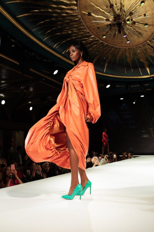 Woman in Orange Long Sleeve Dress Standing on White Floor