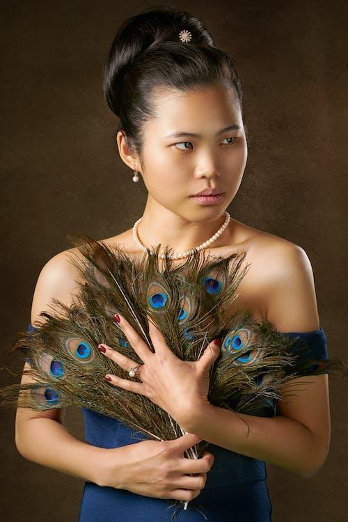 Fotos de stock gratuitas de asiática, bonita, de pie, fondo marrón