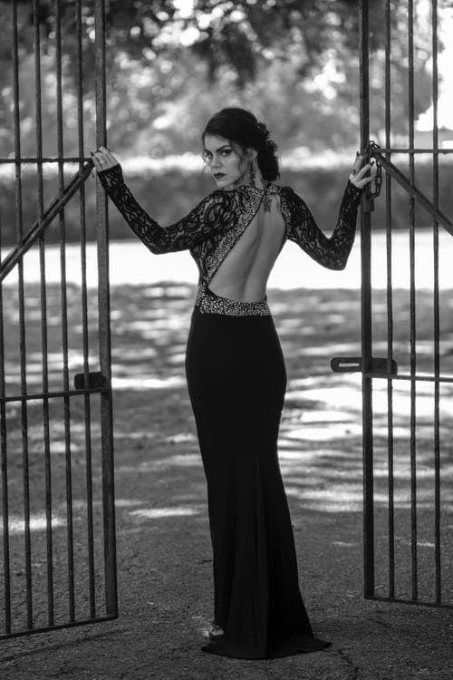 Grayscale Back View Photo of Woman in Elegant Dress Posing by Metal Gate Looking Back