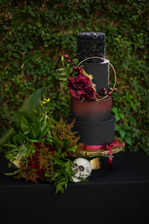 An Artistic Set-up Of A Halloween Decor With Leaves Flowers Skull And a Tier Of Painted Containers