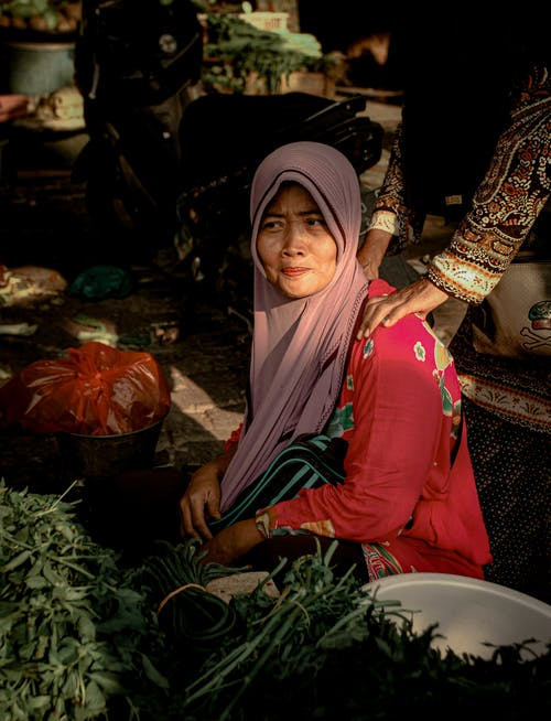 Woman Wearing Pink Hijab In The Market Place Selling Vegetables Getting a Shoulder Massage