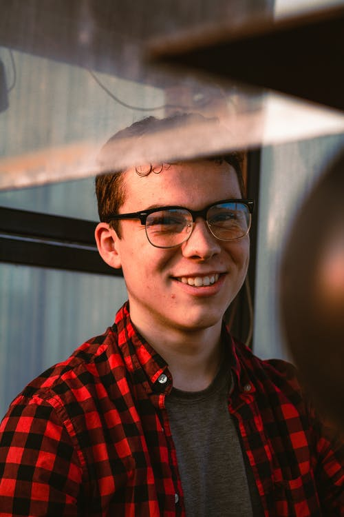 Portrait Photo of Man in Glasses and Red and Black Plaid Shirt Smiling
