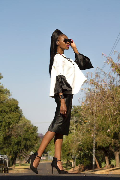 Side View Photo Stylish Woman in White and Black Long-sleeved Blouse and Black Dress Posing In the Middle of the Road