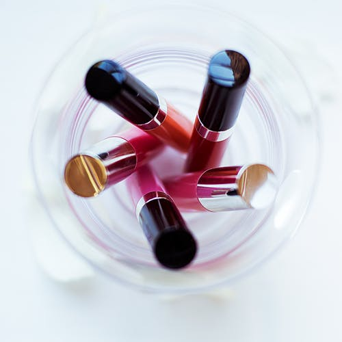 Five Assorted-color Liquid Lipsticks Placed on Glass