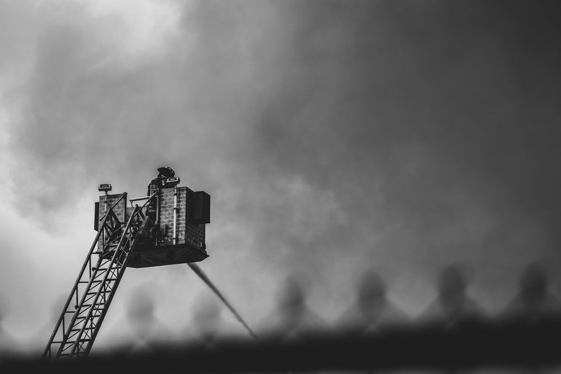 Grayscale Photography of a Fireman On The Fire Truck Ladder Hosing Water Surrounded By Clouds Of Smoke