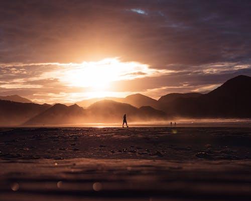 Foto De ángulo Bajo De Gente Caminando Por La Orilla Del Mar, Al Atardecer