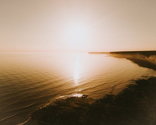 Sun Glaring Over Calm Water Of The Sea And Its Surrounding Landscape