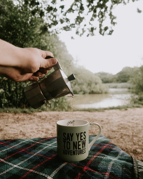 Person Pouring Tea in Cup