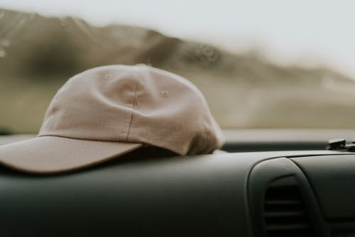 Brown Fitted Cap Near Vehicle Air Vent