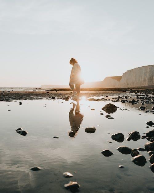 Photo Of Woman Walking On Sea Shore