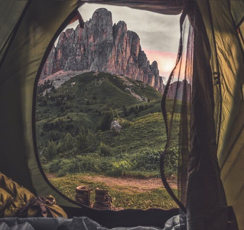 Person on Yellow and Gray Tent Looking at Mountain Scenery