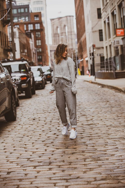 Woman in Gray Sweater and Gray Sweatpants Standing Outdoors