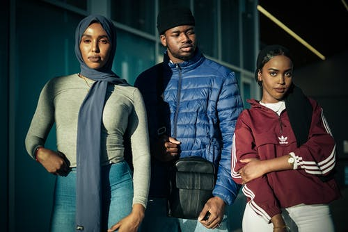 Photo of Two Muslim Women in Hijabs and a Man in a Beanie Hat Posing