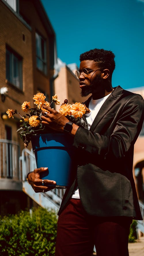 Foto profissional grátis de blazer, carregando, de pé, flores amarelas