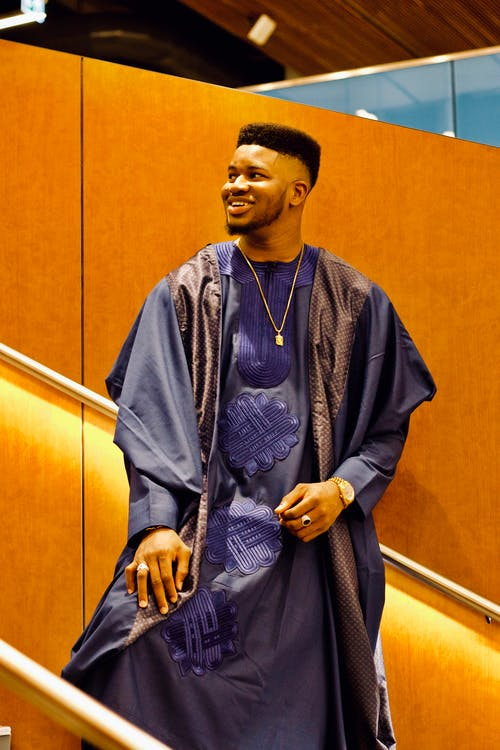 Photo of Smiling Man in Traditional African Wear Standing on Staircase While Looking Away