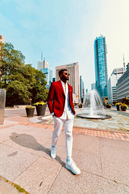 Photo of Man in Red Blazer and White Pants Walking