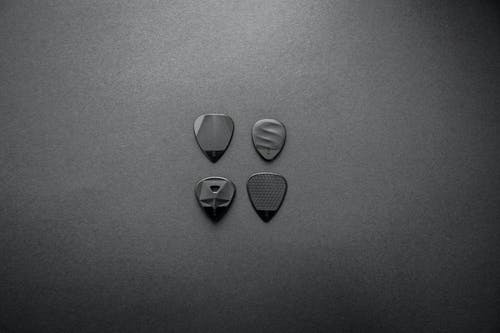 Grayscale Photography of Four Guitar Picks