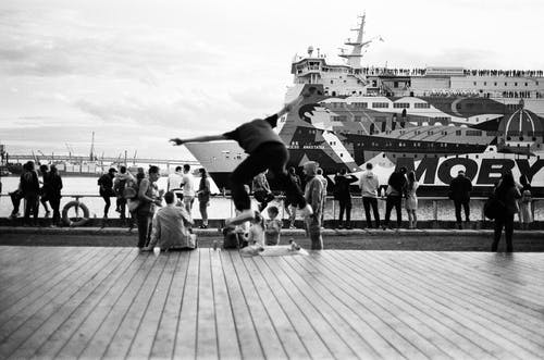 Grayscale Photo of People on Pier