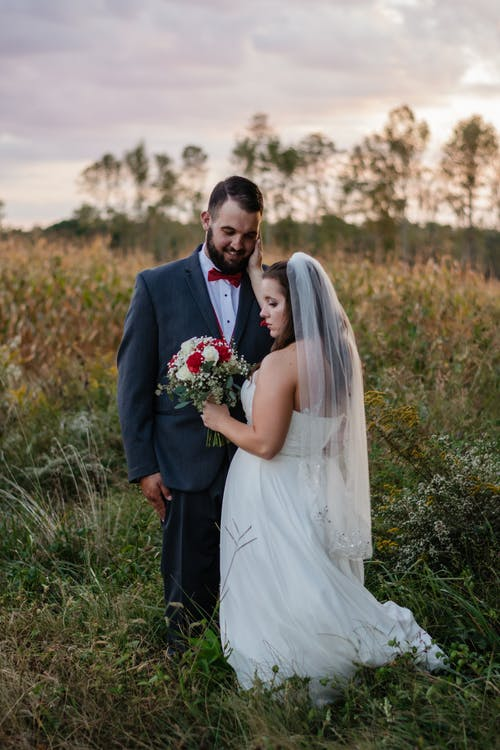 Groom and Bride Standing on Grass