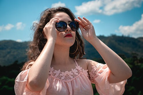 Photo Of Woman Holding Her Shades