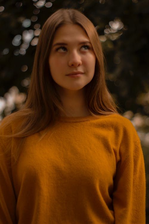 Young Woman in Orange Top With Her Eyes Looking Up