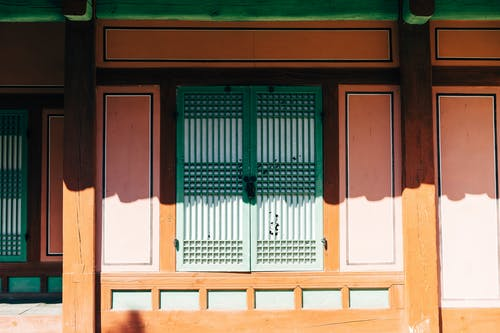 Front Of A House With Green Wooden Window