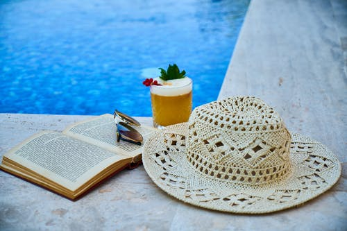 Beige Straw Hat, Book, Sunglasses, and Drink Beside Pool