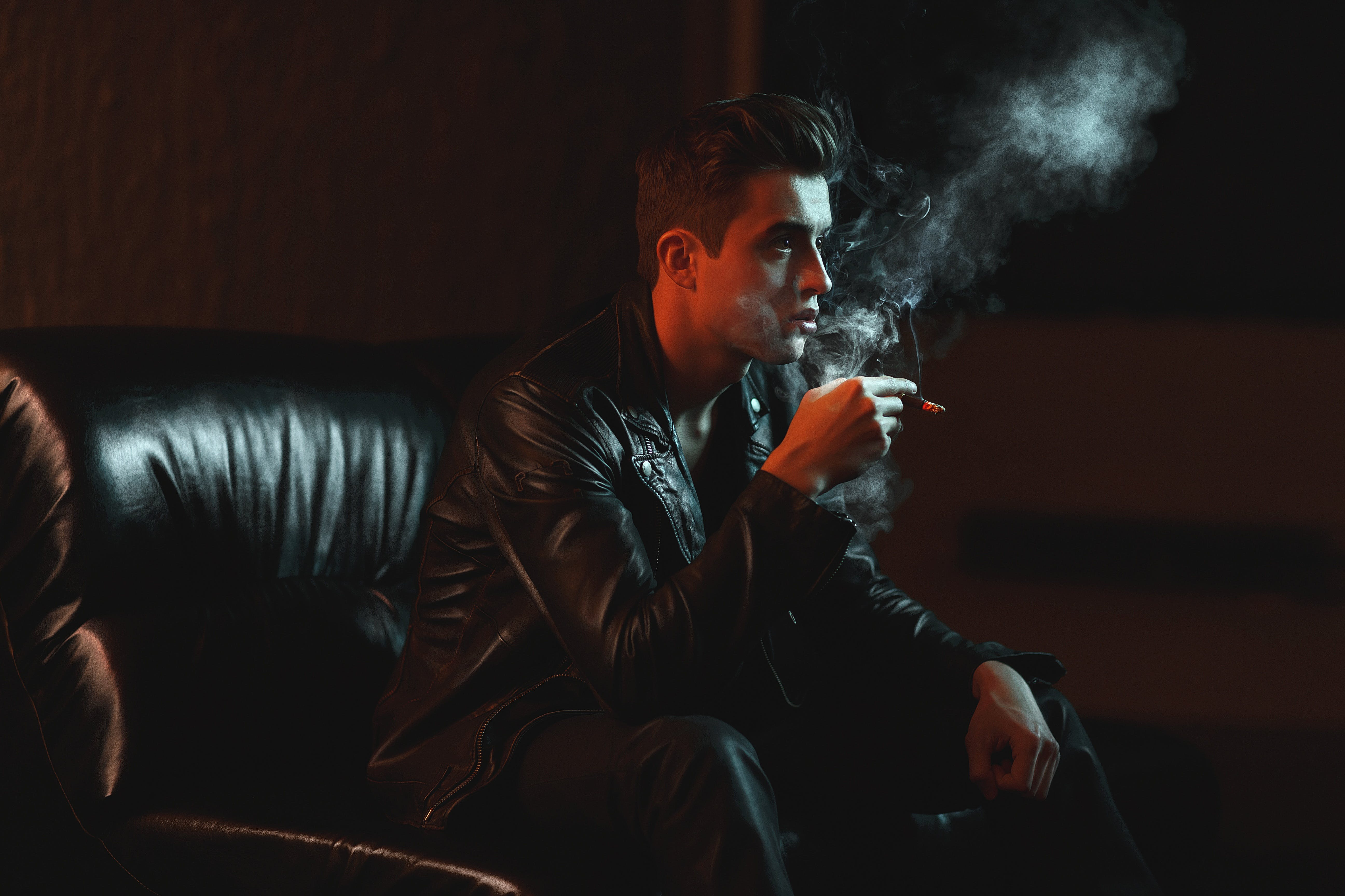 Man Holding Cigarette While Sitting on Sofa