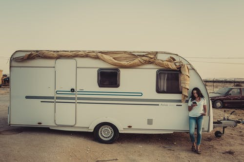 Woman Wearing White Crew Neck Shirt Leaning On Rv Trailer