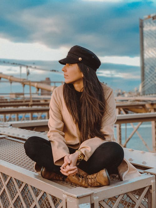 Selective Focus Photo of Woman in Brown Long-sleeved Shirt and Black Cap Sitting on Metal Surface While Looking Away
