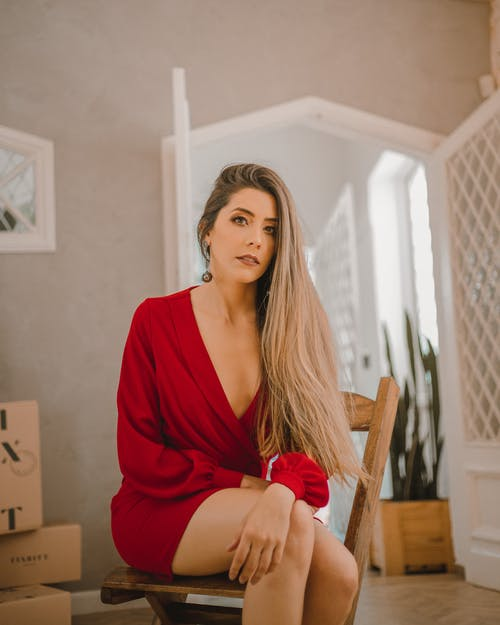 Woman In Red Dress Sitting On Chair
