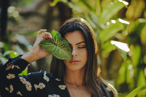 Selective Focus Photo of Woman in Black Floral Top Posing With Her Eyes Closed While Holding Green Leaf Over Right Eye