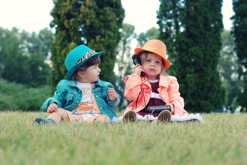 Two Toddlers Sitting on Grass Field