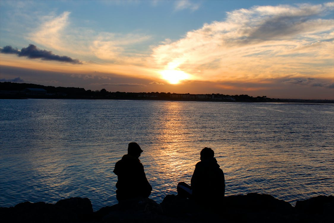 Silhouette of People Sitting on Rock Near Body of Water during Golden Hour