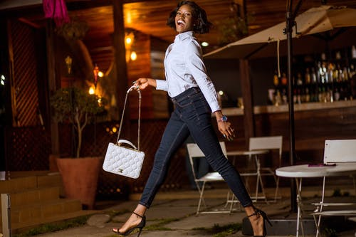 Smiling Woman White Long-sleeved Blouse and Black Denim Fitted Jeans Holding Quilted White Leather Shoulder Bag